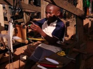 Boy weaving kinta cloth